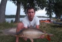 Рыбка держит в руках пойманного на кукурузу карпа